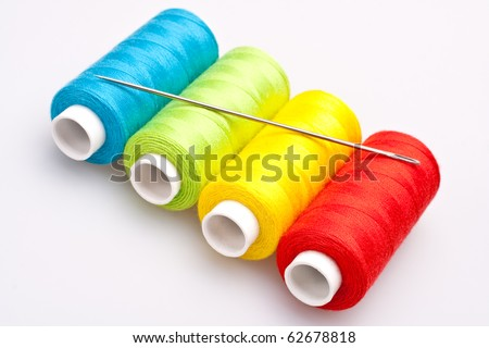 multi-colored rainbow threads for sewing with needle - stock photo
