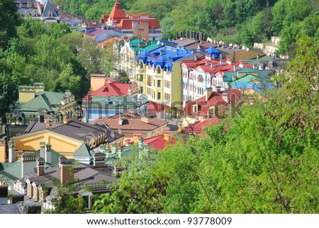 Multi-colored roofs are surrounded by green trees. View from above. - stock photo