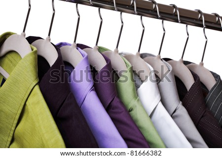 Multi colored shirts on hangers against a white background - stock photo