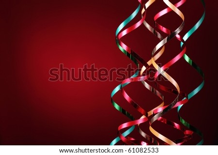 Multi-colored streamers over red background. - stock photo