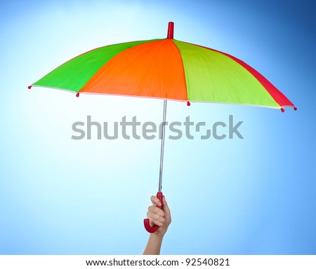 Multi-colored umbrella in hand on blue background - stock photo