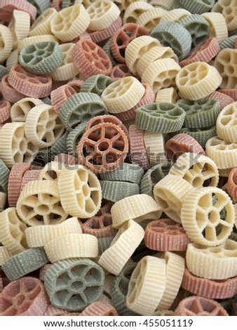 Multi-colored wheel shaped pasta at local market.
