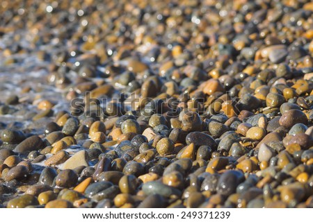 multi colors stones on beach and sea water background - stock photo