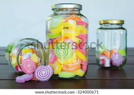 Multi colour candies displayed in glass jars - stock photo