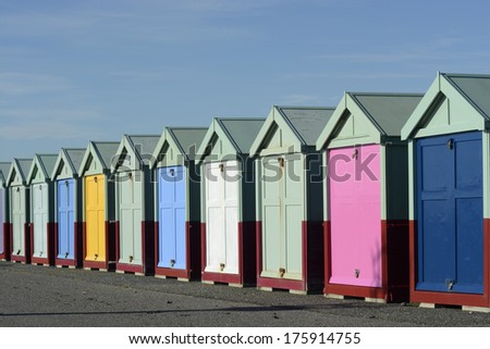 Multi coloured beach huts on the seafront promenade at Brighton, East Sussex, England. - stock photo