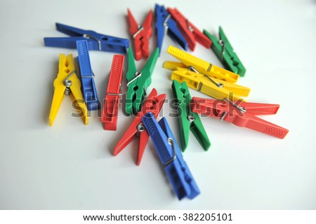 Multi-coloured clothespins scattered randomly on the white background.