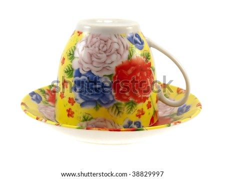 Multi-coloured cup with a saucer isolated on a white background