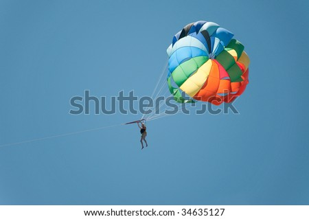 Multi coloured parachute over the blue sky - stock photo