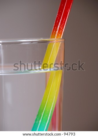 Multi coloured pencil in a glass of water, depicting refraction, illusion. - stock photo