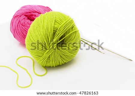 Multi-coloured threads for sewing, needles, a measuring tape on a white canvas - stock photo