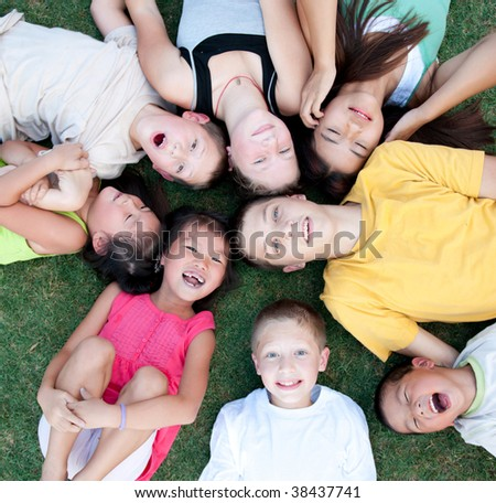 Multi-ethnic adopted brothers and sisters lying on the grass. - stock photo