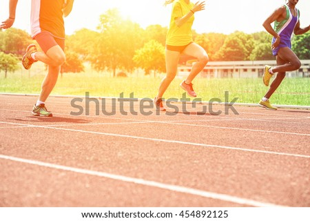 Multi-ethnic athletes running on athletic racetrack at sunset - Three runners sprinting for training with back lighting - Sport competition and healthy lifestyle concept - Warm filter with vivid tones - stock photo