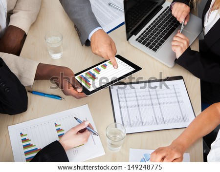 Multi Ethnic Business Colleagues Discussing Graph On Digital Tablet - stock photo