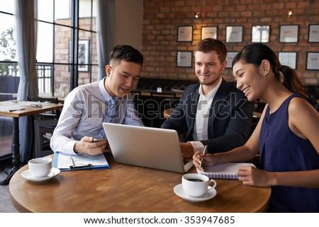 Multi-ethnic business colleagues discussing information on laptop