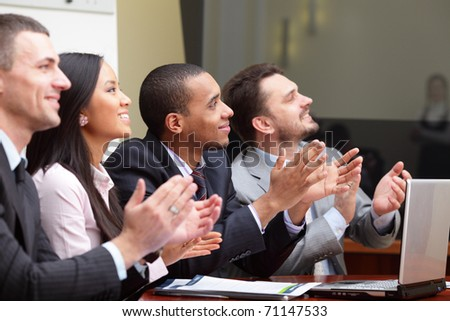 Multi ethnic business group greets somebody with clapping and smiling. Focus on african-american man - stock photo