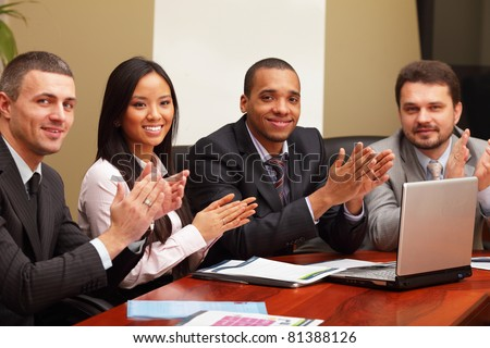 Multi ethnic business group greets you with clapping and smiling. Focus on asian woman - stock photo