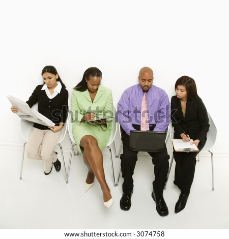 Multi-ethnic business group of men and women sitting looking at laptop and papers.
