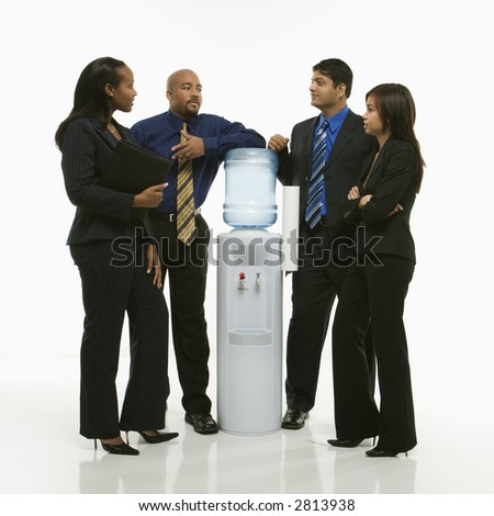Multi-ethnic business group of men and women standing at water cooler conversing. - stock photo