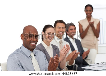 Multi-ethnic business people applauding after a presentation in the office - stock photo