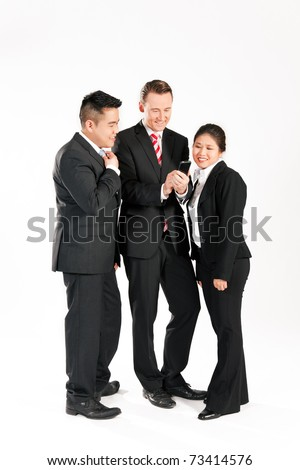 Multi-ethnic business people standing together and looking at a mobile phone