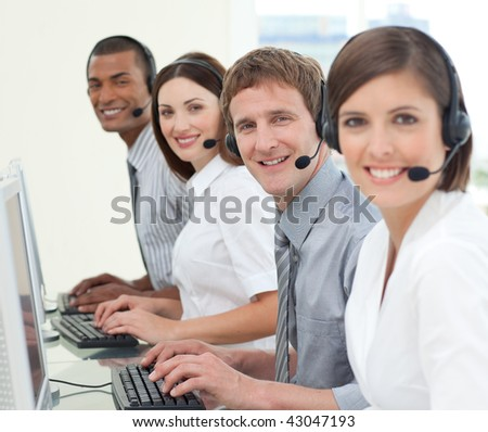 Multi-ethnic business people with headset on working in a call center - stock photo