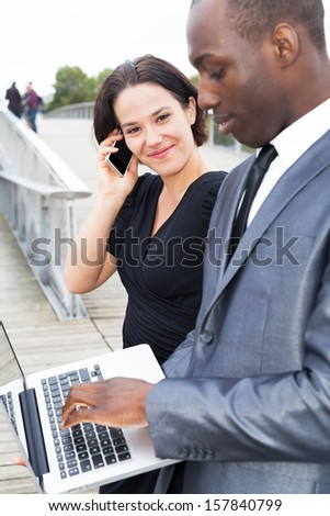 Multi ethnic business people working outdoors, woman phoning and man on laptop