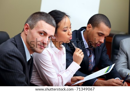 Multi ethnic business team at a meeting. Focus on woman - stock photo