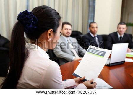 Multi ethnic business team at a meeting. Woman presenting her project. Focus on woman - stock photo
