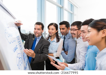 Multi-ethnic business team gathered around whiteboard with infographics