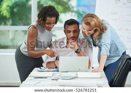 Multi-ethnic business team gathered at laptop