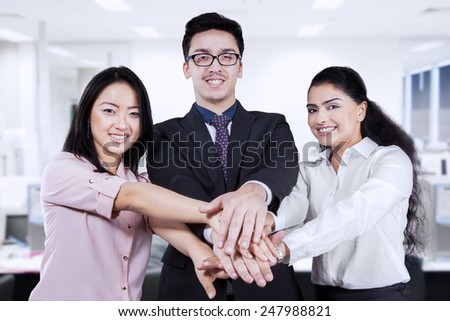 Multi ethnic business team smiling at the camera while joining their hands in the workplace