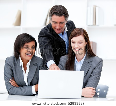 Multi-ethnic business team working at a computer in the office - stock photo