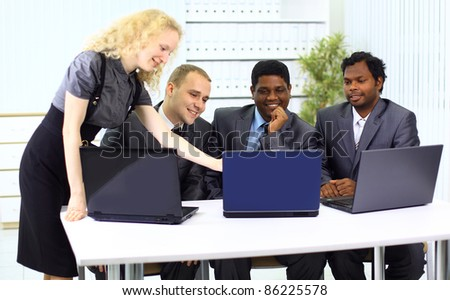 multi ethnic business team working on laptop. - stock photo