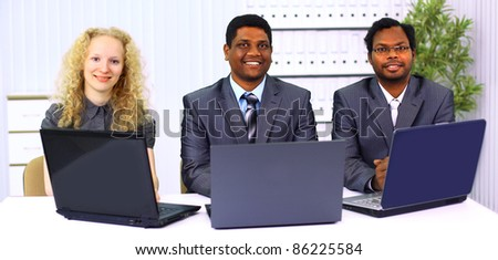 multi ethnic business team working on laptop.