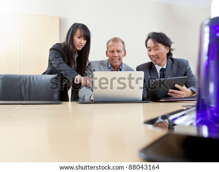 Multi ethnic business team working on laptop - stock photo