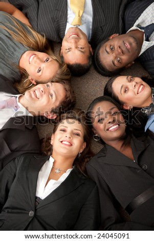 Multi-ethnic business teamwork in an office with heads together on the floor