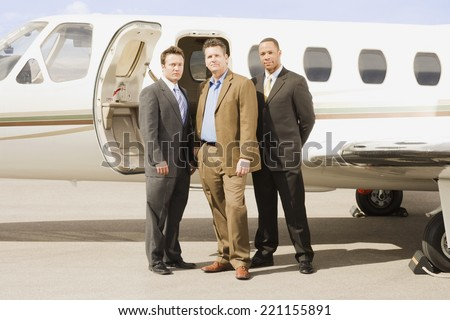 Multi-ethnic businessmen in front of airplane - stock photo