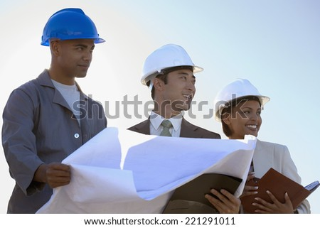 Multi-ethnic businesspeople and construction worker with blueprints - stock photo