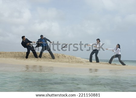 Multi-ethnic businesspeople having tug of war - stock photo
