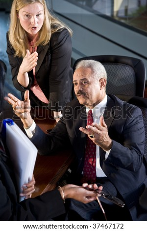 Multi-ethnic businesspeople in boardroom having a serious conversation - stock photo