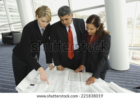 Multi-ethnic businesspeople looking at blueprints - stock photo