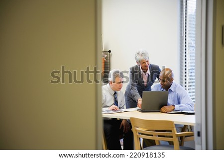 Multi-ethnic businesspeople looking at laptop - stock photo