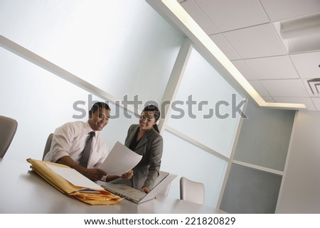 Multi-ethnic businesspeople looking at paperwork - stock photo