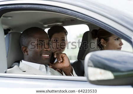 Multi-ethnic businesspeople sharing a car - stock photo