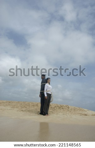 Multi-ethnic businesspeople tied together at beach - stock photo