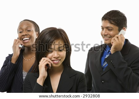 Multi-ethnic businesswomen and businessman standing talking on cell phones.