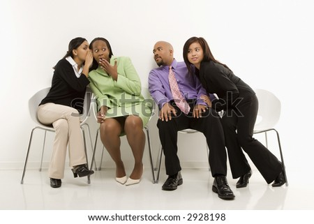 Multi-ethnic businesswomen whispering and making faces while colleagues eavesdrop. - stock photo