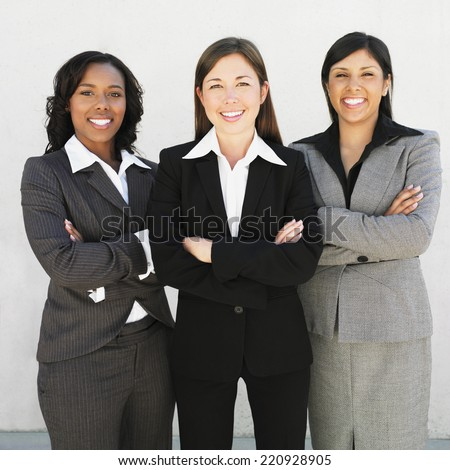 Multi-ethnic businesswomen with arms crossed - stock photo