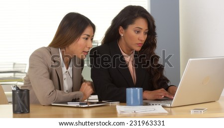 Multi-ethnic businesswomen working on laptop - stock photo