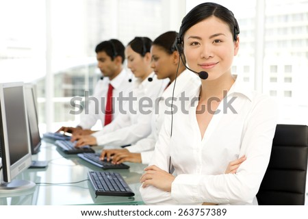 Multi ethnic Call Center. Selective focus on Asian woman with arms crossed on foreground. - stock photo